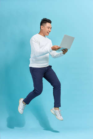 Full length portrait of happy man jumping and holding laptop isolated over blue background