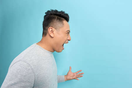 Closeup side view profile portrait of angry upset young man isolated on blue background.