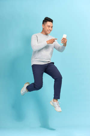 Full length of handsome young man taking phone while jumping against blue background. Standard-Bild