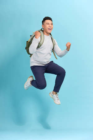 Happy young attractive man jumping and waving his hand, wearing in basic clothes with backpack Banco de Imagens