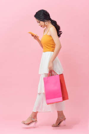 Woman carrying shopping bags and text messaging on the phone