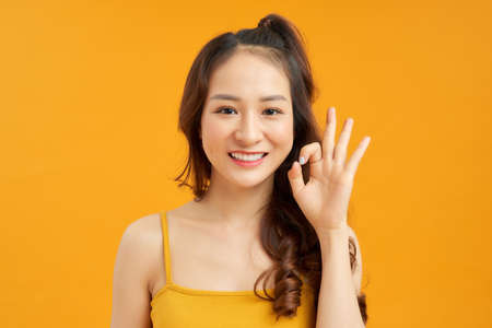 Portrait of a smiling woman showing ok sign with fingers isolated on a yellow background