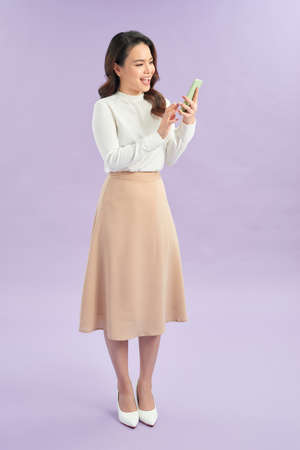 Portrait of a cheerful girl looking at mobile phone isolated over purple background Banque d'images