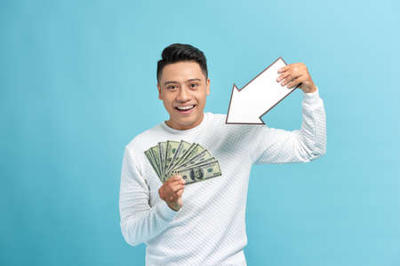Man holding money and white arrow over blue background Stock Photo