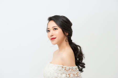 The bride in a magnificent white dress stands back and looks over her shoulder.