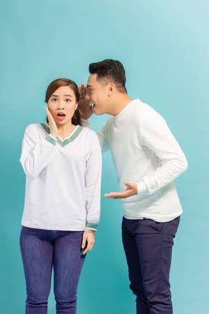 Asian man sharing secret or whispering gossips into his girlfriend's ear, blue studio background Foto de archivo