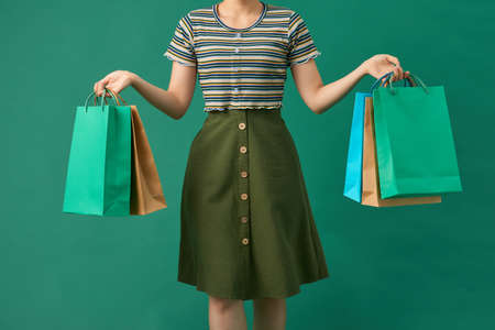 Beautiful young asian woman with colored shopping bags over green background