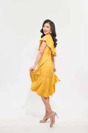 Portrait of a beautiful young woman in yellow dress and turn around.