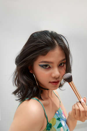 Young Woman Making Makeup Using Cosmetic Brush Posing On white Background.