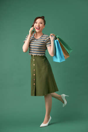 Portrait of happy young with shopping bags woman talking on cellphone