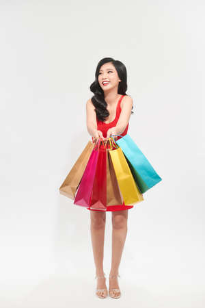 Shopping woman walking and holding bags over white
