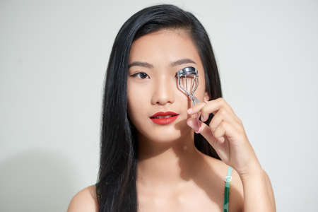 Asian woman corrects eyelashes with curling tongs, close up