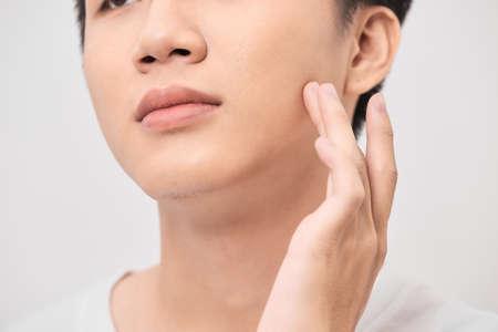 Handsome man touching his face close up portrait studio on white background Reklamní fotografie