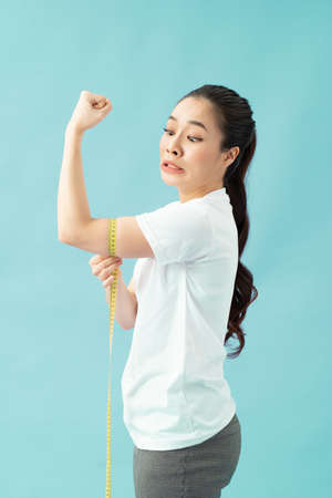 Young beautiful woman over isolated blue background surprised with a measuring tape around her arm