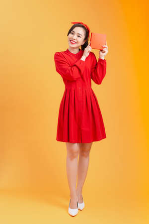 Happy young Asian woman showing gift box over orange background. Birthday, christmas, holiday, anniversary concept.