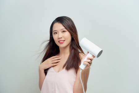 Portrait of happy young woman blow-dry Stock Photo