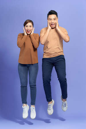 Happy couple shouting and touching cheeks while jumping with spreading legs isolated over purple background