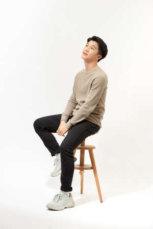 Full body portrait of handsome young Southeast Asian man sitting on high chair,