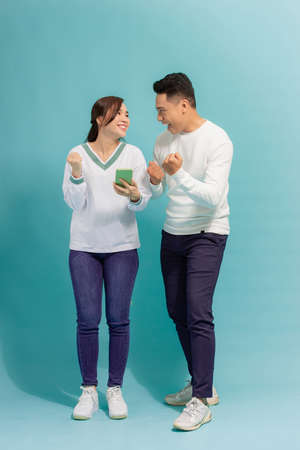 Asian young couple standing looking at the screen of a smart phone expression of surprise with an isolated background Reklamní fotografie