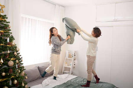 Two girl friends enjoying pillow fight jumping on bed