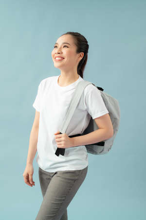 Portrait of energetic teenager girl isolated on blue background pulling forward straps of gray hipster backpack,