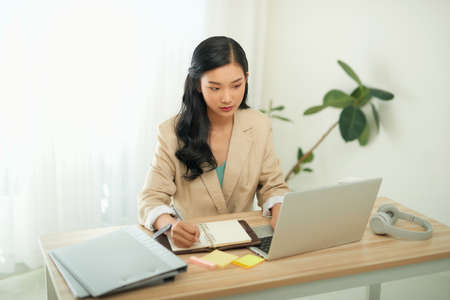 Asian businesswoman mother working at home with notebook computer. Concept for home based work.