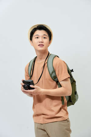 Portrait of cheerful young Asian tourist man holding digital camera and taking photo when standing over white background.