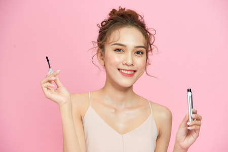 Closeup attractive young woman hold mascara brush in hands and smile isolated on pink background.