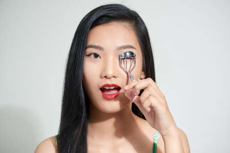 teen girl making her eyelashes wider with with curler Stock Photo