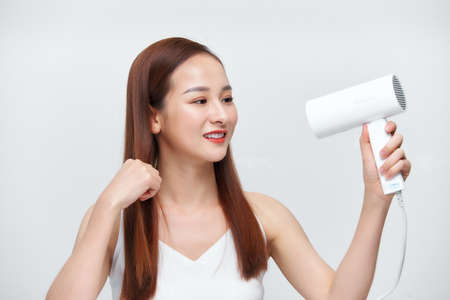 Beautiful Smiling Woman Drying Healthy Long Straight Hair Using Hair Dryer.