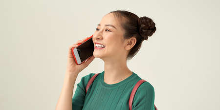 Woman model speaks on the phone, holding a backpack on her shoulder