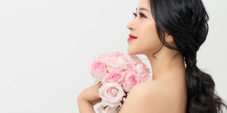Portrait of a beautiful girl with a bouquet of roses. Beauty and fashion.
