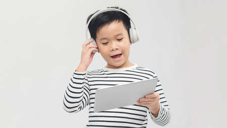 a lovely young pupil rejoicing and jumping with his tablet wearing headphones and smiling 免版税图像