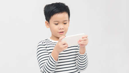 Asian child focused and concentrated playing with mobile phone  in kid suffering gaming addiction concept 免版税图像 - 164888950