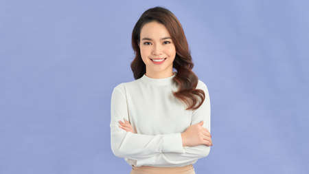 Portrait of a happy woman standing with arms folded isolated on a purple background