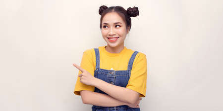 Photo of happy young woman standing isolated over white wall background. Looking camera showing copyspace pointing. 免版税图像 - 164888952