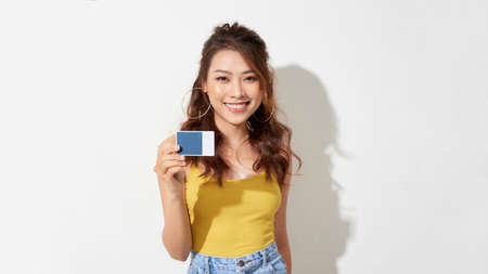 Smiling Pretty asian woman holding credit card while rejoices and looking at the camera over white background