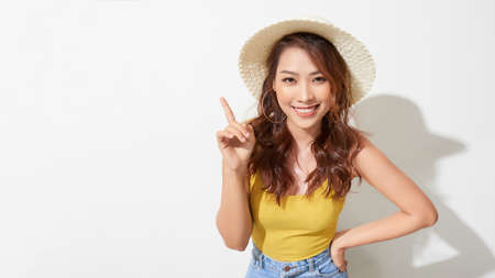Young beautiful asian woman wearing summer hat pointing up while smiling confident and happy.