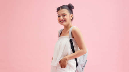 Friendly woman wearing backpack standing isolated on pink background.