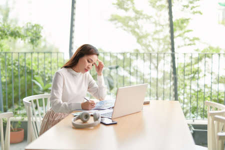 Portrait of beautiful confident woman is sitting at the table in front of computer and checking information in her diary and on the internet