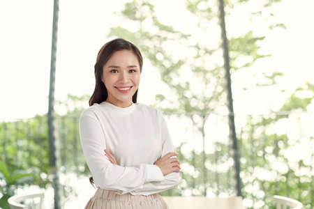 Happy young beautiful Asian woman with brace retainers, standing arms crossed, smiling to camera in modern office with big glass window and blur green background