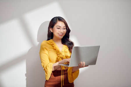 Portrait of a happy asian businesswoman holding laptop computer and looking away solated over white background