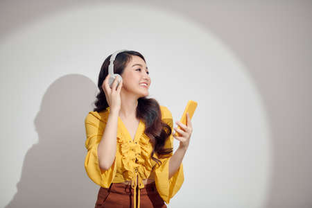 young beautiful girl listening to music through the headset and looking at her smart phone against white background 免版税图像 - 164880806