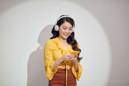 Cheerful woman listening to music with headphones isolated over white background, holding mobile phone 免版税图像 - 164880807