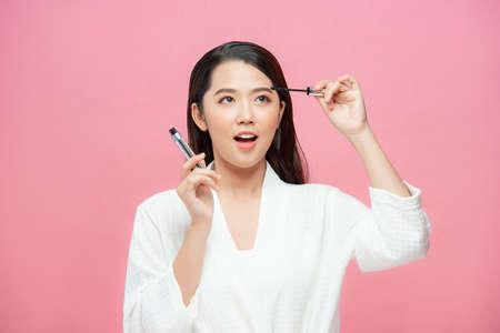 Asian woman putting mascara on eyelashes on pink background