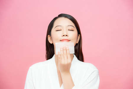 Closeup of beautiful happy asian girl model with natural makeup using oil absorbing sheets, beauty product at studio 免版税图像 - 164649246
