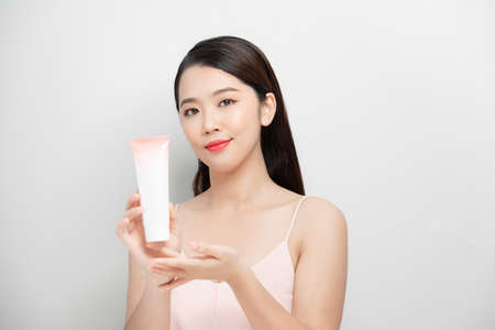Beautiful woman shows the bottle of skincare on a gray background. 免版税图像