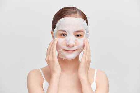 Happy young Asian woman using cosmetic mask isolated over white background.