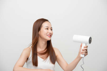 Beautiful Attractive Asian woman smile and holding hair dryer feeling so confident and happiness 免版税图像 - 164694937