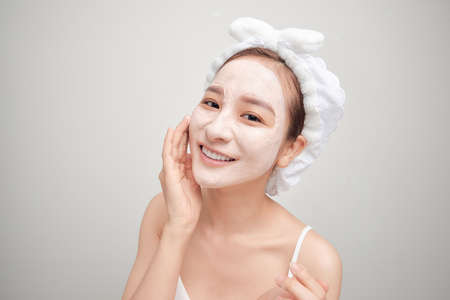 Young Asian woman applying facial clay mask over white background. Beauty treatments concept.